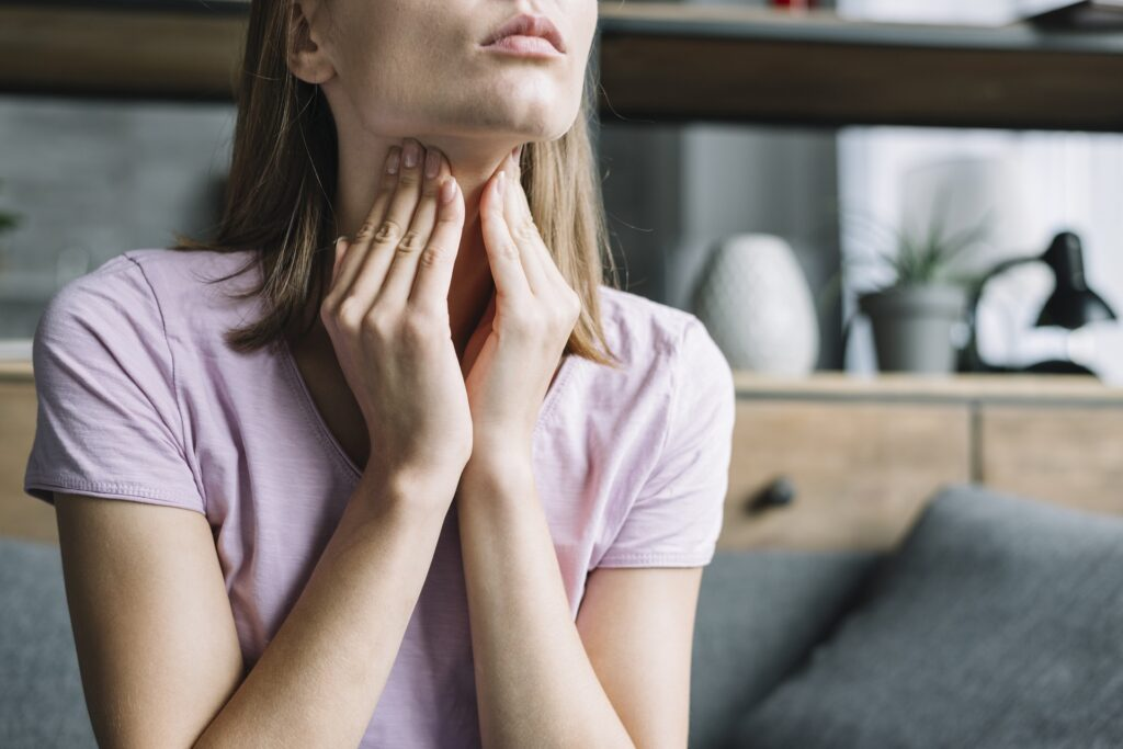 Woman feeling her neck where the thyroid gland is