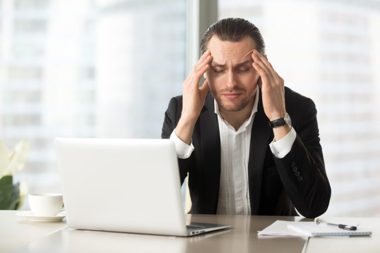 Businessman at work with his hands on his temples due to a headache from anxiety