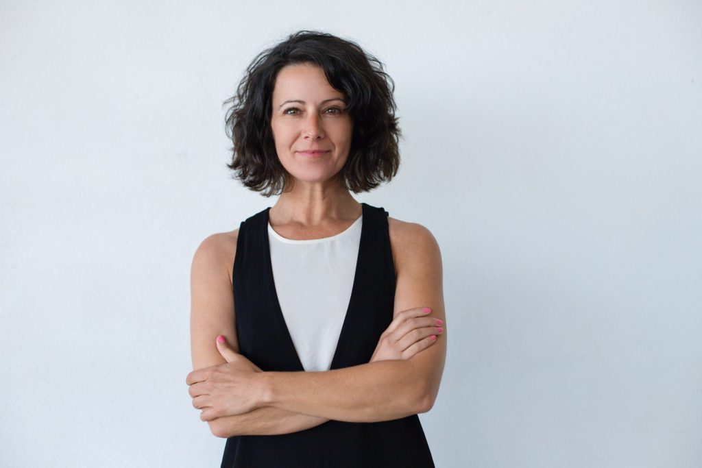 Cheerful middle aged woman with curly hair. Portrait of attractive brunette woman standing with crossed arms and smiling at camera isolated on grey background. Emotion concept