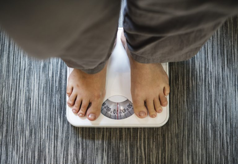 Woman standing on a scale, weight gain due to an autoimmune disorder