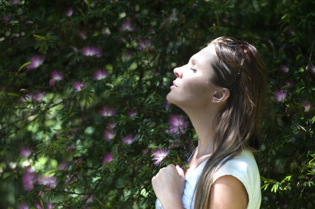 Woman taking a deep breath outside near plants and trees
