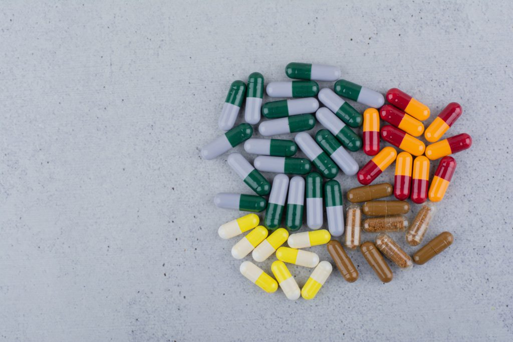 Assorted medical capsules on a marble surface.