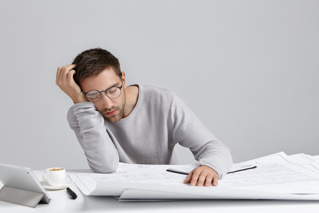 Tired young attractive man sleeps at work place, has much work, being fatigue and exhausted, isolated over white studio background. Sleepy male engineer has deadline, busy all day, has sleppless night