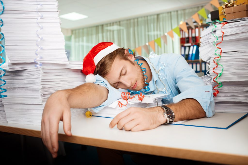 Tired young handsome businessman in red santa claus hat sleeping at workplace among papers on christmas day.
