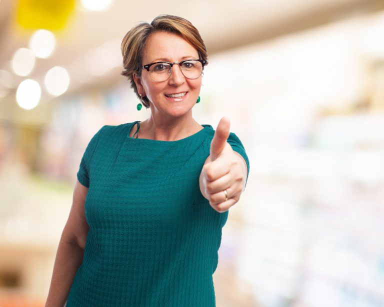 portrait of a mature woman with thumbs up