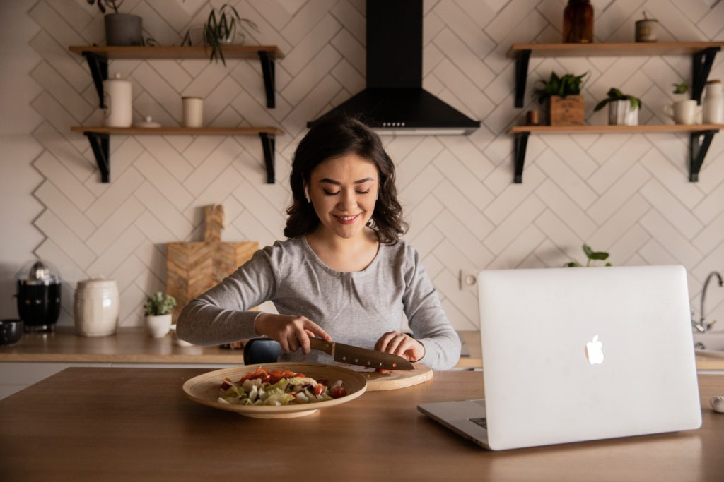 Woman cooking a meal at home in front of her laptop