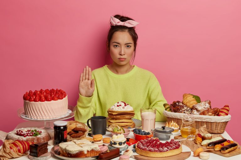 Young woman looking serious with unhealthy food infront of her